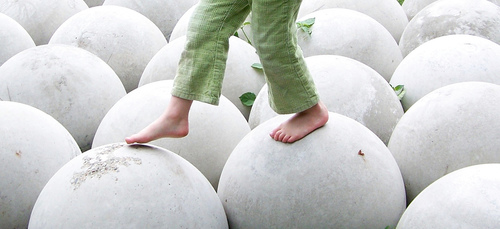 Free Child Walking On White Round Spheres Balance